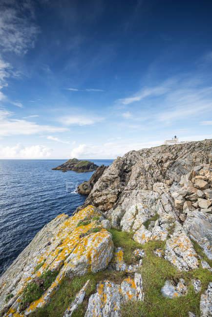 Royaume-Uni, Écosse, Sutherland, Paysage côtier accidenté avec le phare de Strathy Point en face de la mer du Nord — Photo de stock