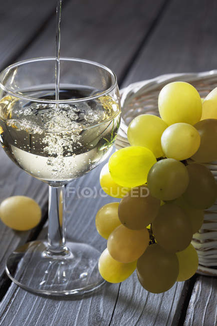 Pouring white wine into wine glass on table with grapes — Stock Photo