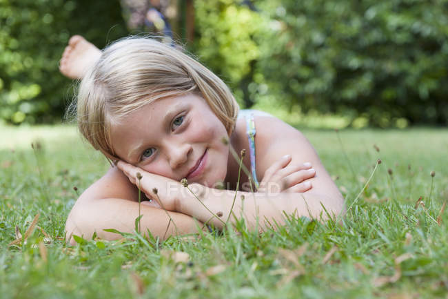 Smiling cute girl lying in grass — Stock Photo