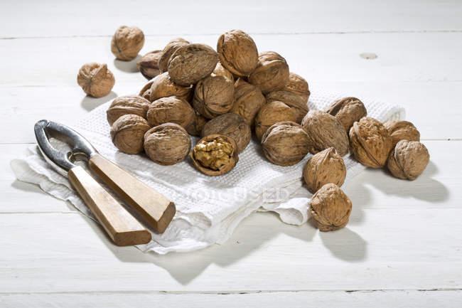 Волоські горіхи з Лускунчик і блюдо рушник на білий дерев'яний стіл — стокове фото