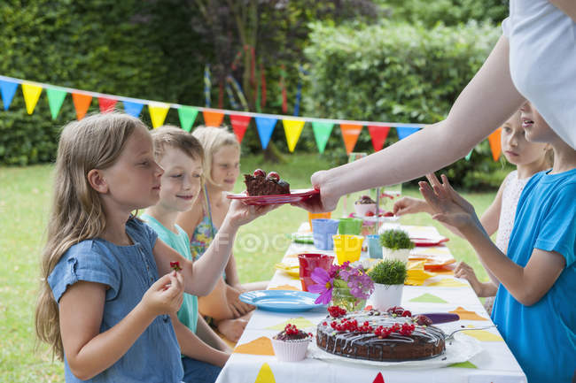 Girl receiving piece of cake on a birthday party — Stock Photo