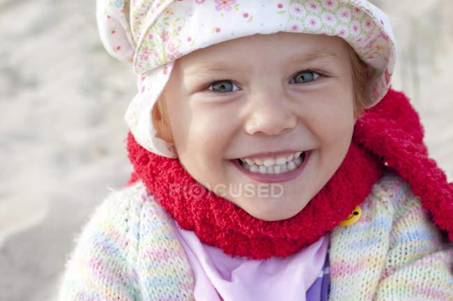 Улыбающаяся маленькая девочка на пляже смотрит в камеру — стоковое фото
