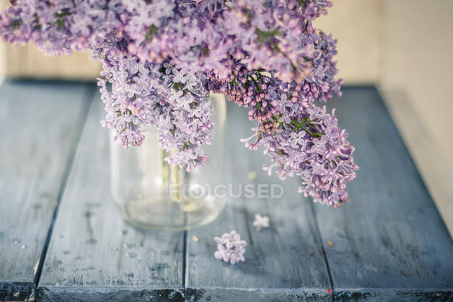 Lilac flower in vase on blue wooden board — Stock Photo