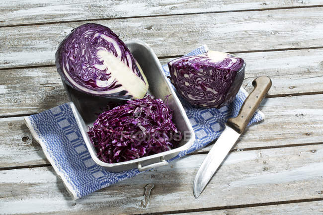 Red cabbage, kitchen knife and kitchen towel on wooden table — Stock Photo