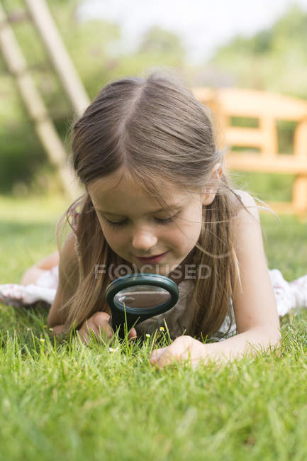 Girl looking through magnifying glass in garden — Stock Photo