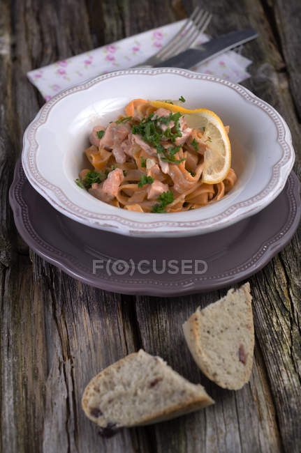 Homemade tomato tagliatelle with salmon cream sauce in plate on wood — Stock Photo