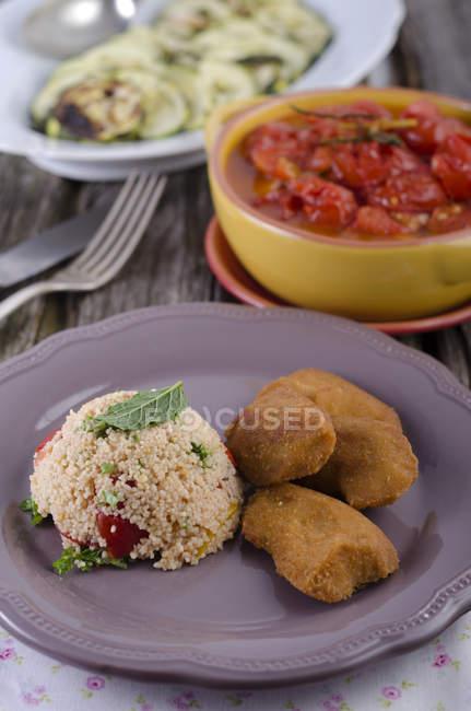 Вегетарианская самородки с кускусом салат, цуккини и помидоры соленые — стоковое фото