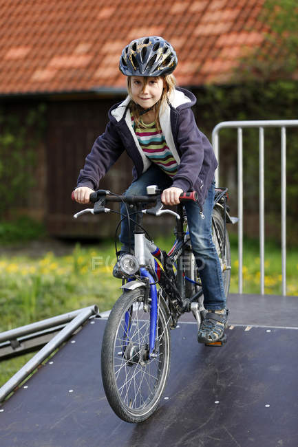 Portrait of girl riding bicycle on ramp — Stock Photo