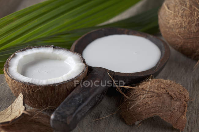 Close-up of Half coconut with coconut milk in wooden scoop on dark wood with leaf — Stock Photo