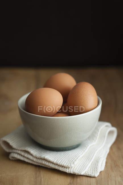Tigela de ovos castanhos na mesa, close-up — Fotografia de Stock