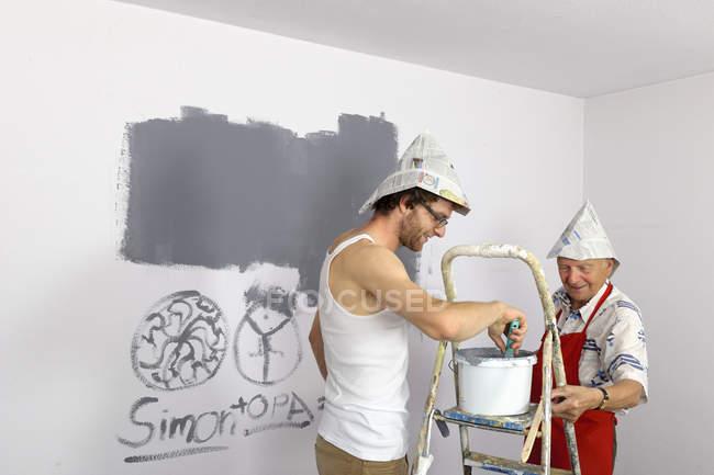 Дідусь і онук носінні шапки папір живопис стін — стокове фото