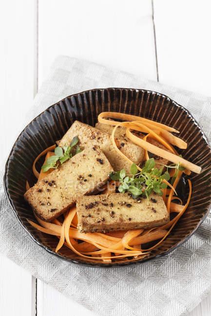 Fritto marinato tofu con insalata di carote in piatto di legno bianco con tessuto — Foto stock