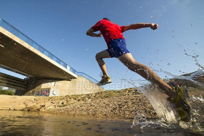 Jovem atlético correndo através do rio Rems — Fotografia de Stock