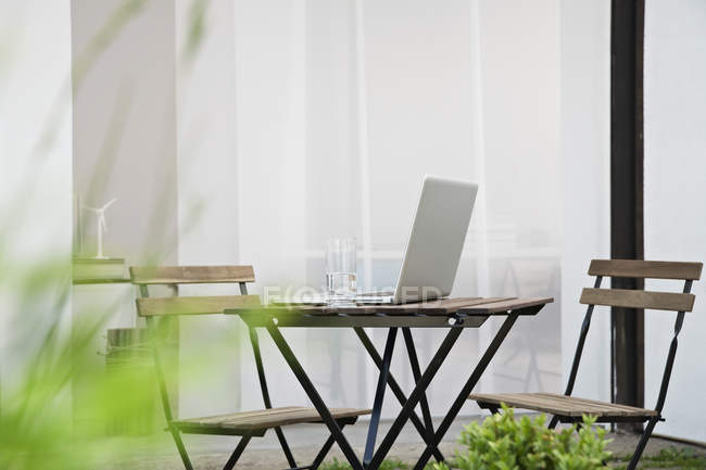 Opedned  Laptop on table with water glass — Stock Photo