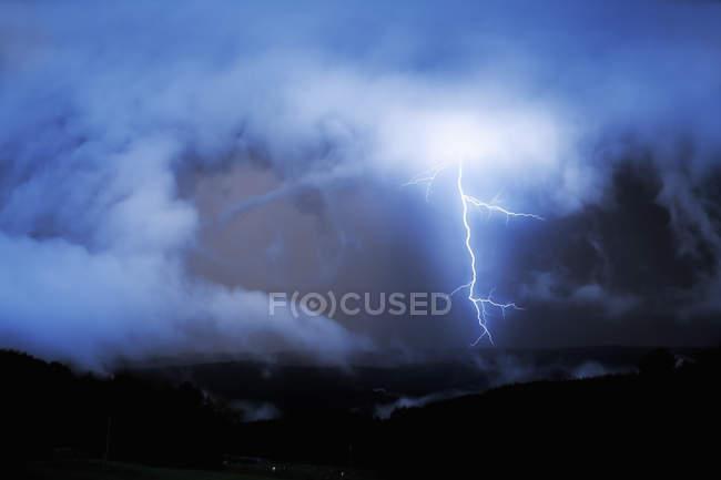 Vista panoramica di un fulmine in un cielo nuvoloso mentre temporale colpisce — Foto stock