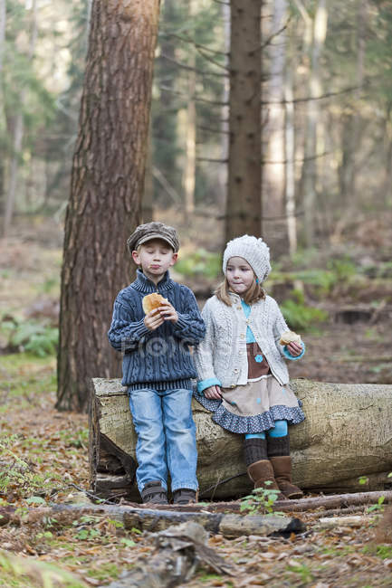 Brother and sister eating bread in woods — Stock Photo