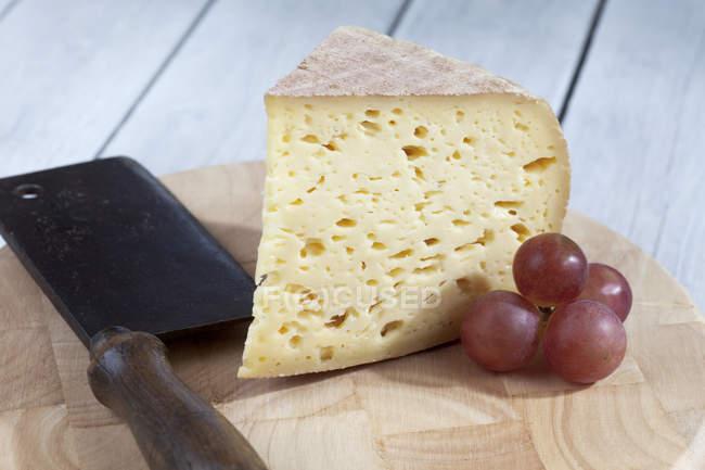 Primer plano de Bethmale pedazo de queso con uvas de tabla de madera con cuchillo - foto de stock