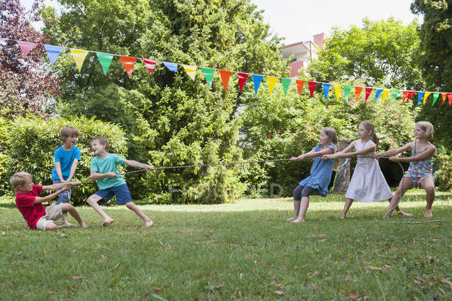 Children playing tug-of-war on a birthday party — Stock Photo