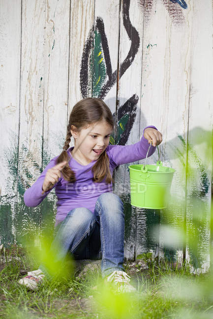 Girl playing with bucket on grass in playground — Stock Photo