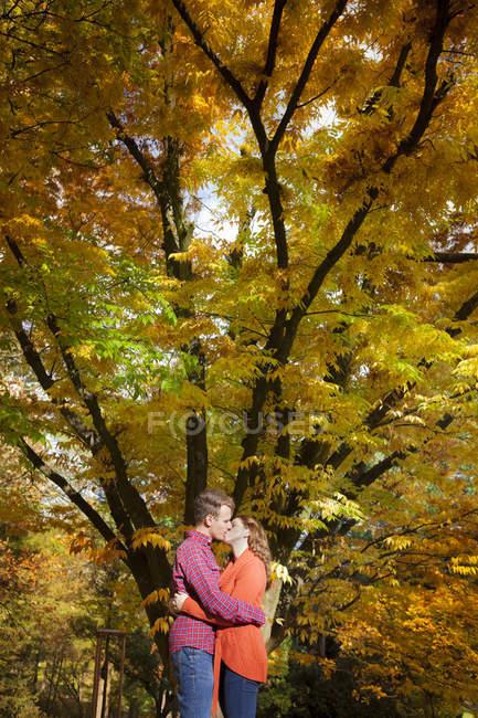 Joyeux jeune couple embrasser dans le parc automnal — Photo de stock