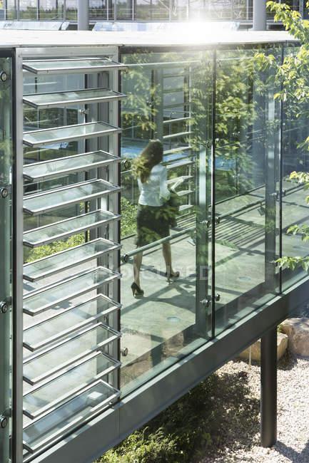 Donna di affari che cammina in ufficio con finestre di vetro — Foto stock