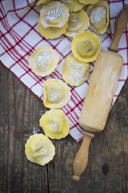 Фаршировані тісто, рушник блюдо і дерев'яні качалкою на дерев'яні таблиці — стокове фото