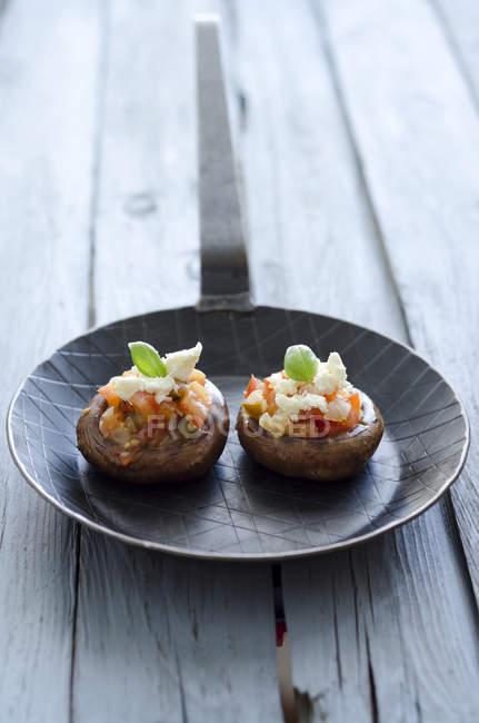 Грибы, наполненные помидоры и сыр фета сыр в сковороде на дереве — стоковое фото