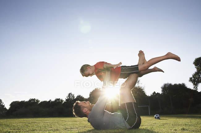 Padre che tiene il figlio in alto sul campo di calcio — Foto stock