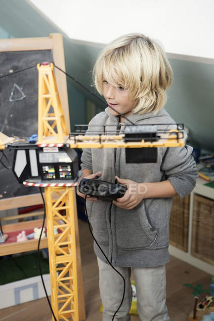 Блондинка хлопчик грає з іграшкою кран — стокове фото