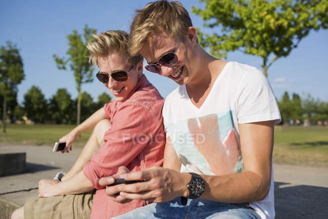 Alemanha, Dois jovens sentados na parede usando seus telefones inteligentes — Fotografia de Stock