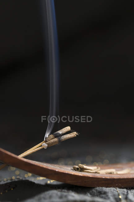 Detalle de porta madera y varillas de incienso con humo - foto de stock