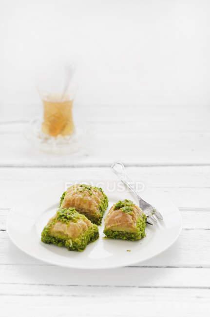 Плиты турецкой пахлавы и стакан чая на деревянный стол, крупным планом — стоковое фото