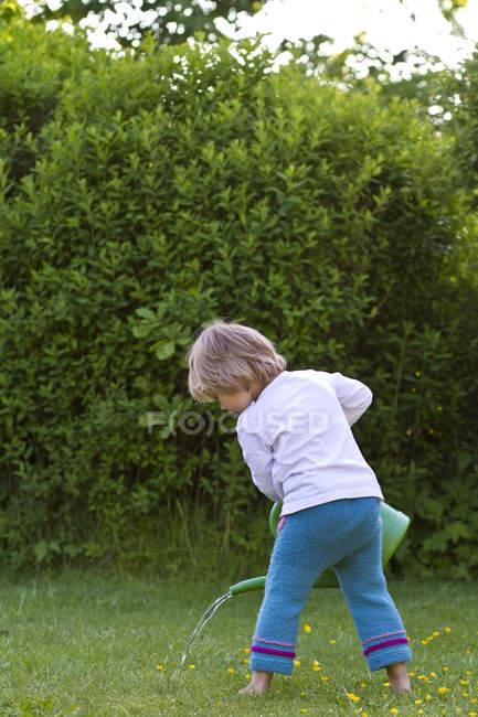 Little girl watering lawn in garden — Stock Photo