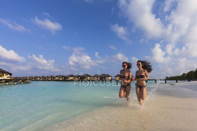 Maldive, giovane donna e ragazza adolescente che funzionano sulla spiaggia — Foto stock