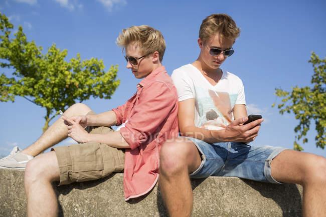 Due giovani uomini seduti sul muro con i loro smartphone — Foto stock