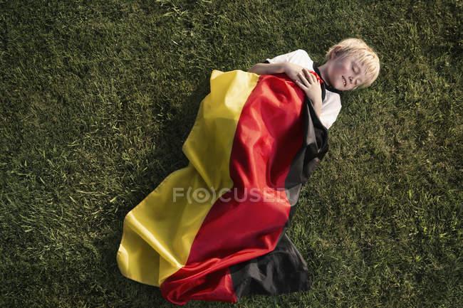 Jungen Fußball Fan schlafen eingewickelt in deutsche Flagge — Stockfoto