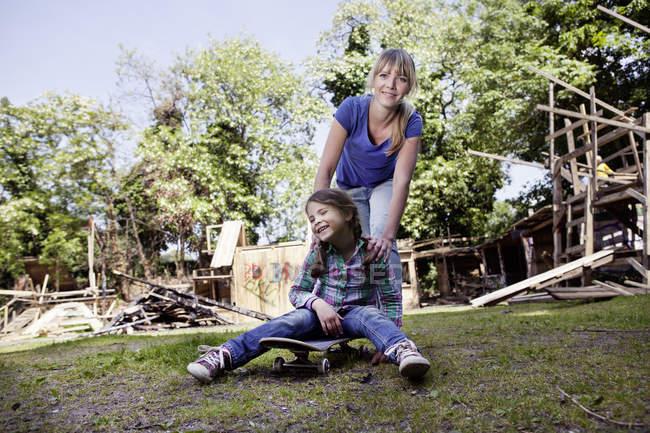 Madre e hija jugando con monopatín, sonriendo - foto de stock