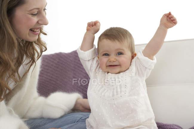 Lächelndes Babymädchen mit ausgestreckten Armen neben ihrer Mutter zu Hause — Stockfoto