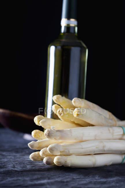 Кучу белая спаржа с бутылкой вина на темном фоне — стоковое фото