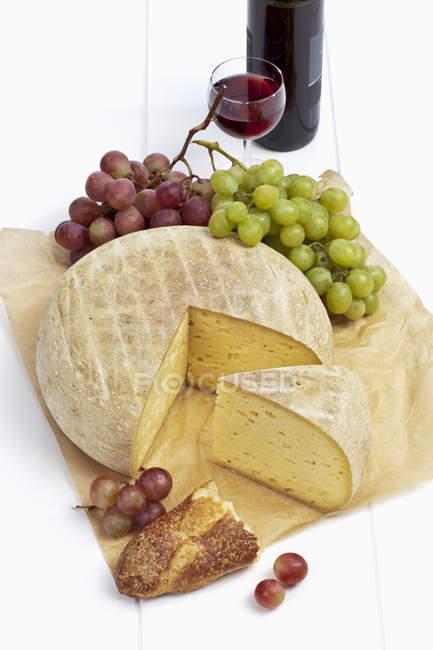 Queso francés Bethmale con Copa de vino tinto, botella de vino, baguette y uvas en pergamino - foto de stock