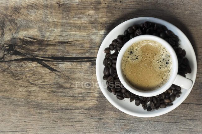 Cup of coffee and saucer with coffee beans on wooden table — Stock Photo