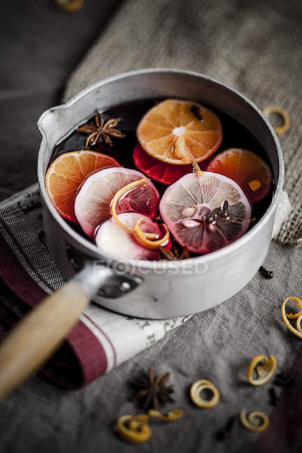 Casserole with mulled wine, slices of lemons and oranges and spices — Stock Photo