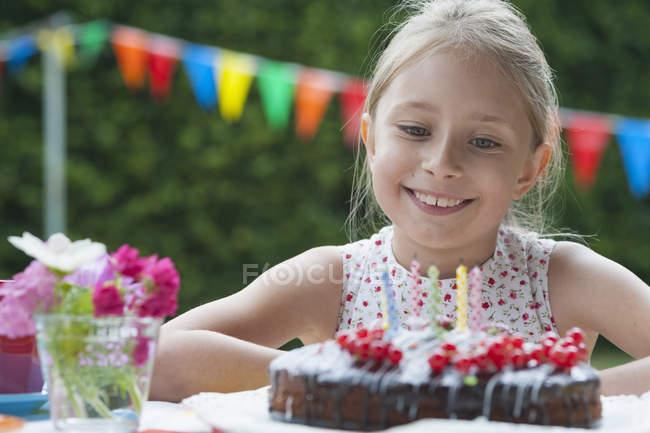 Счастливая девушка на дне рождения смотрит на торт — стоковое фото