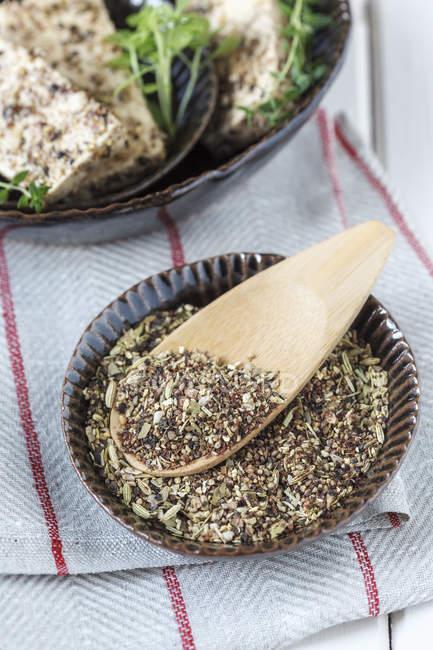 Miscela di spezie in ciotola, tofu marinato in sfondo, colpo dello studio — Foto stock
