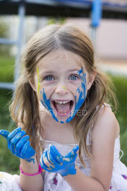Retrato de niña jugando con pintura de dedos, sonriendo - foto de stock