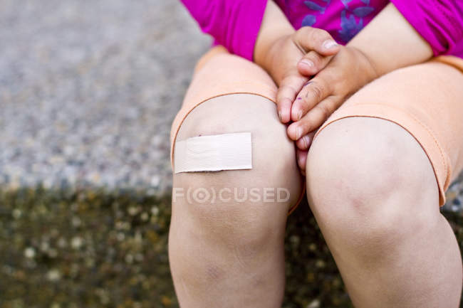 Close-up of girl sitting with patch on knee — Stock Photo