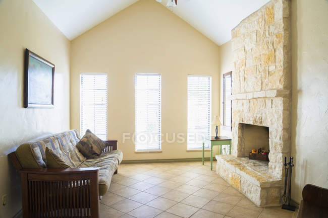 Daytime interior view of a couch with pillows in front of a fireplace — Stock Photo