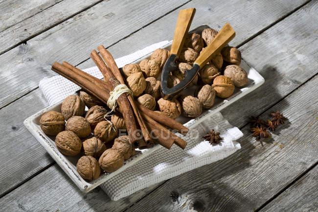 Палички блюдо з горіхами, кориці, зірки анісу, Лускунчик і блюдо рушники на дерев'яну столову — стокове фото