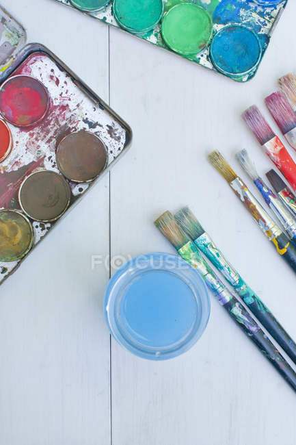 Watercolours with paintbrush on white surface, close up — Stock Photo