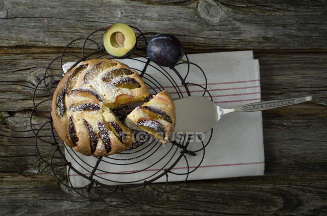 Torta de ciruela casera en refrigeración servidor rack y pastel en la mesa de madera - foto de stock